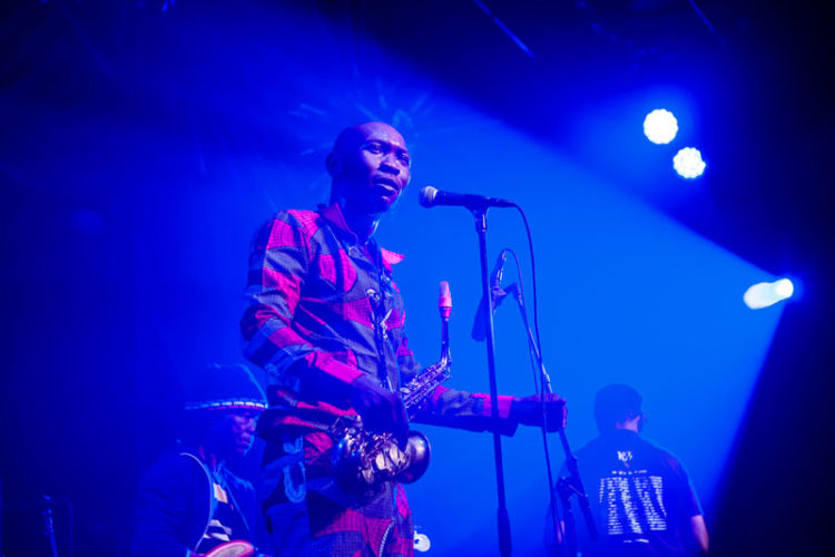 Seun Kuti on stage holding a saxophone